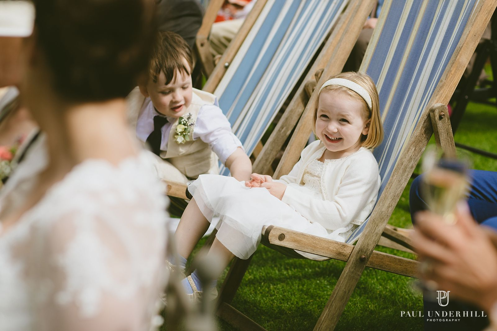 Flower girl sat on chair outside at Larmer Tree